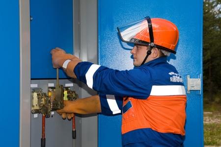 electrical circuit: Elettricista in tuta blu e un casco protettivo spegnere la luce alla sottostazione