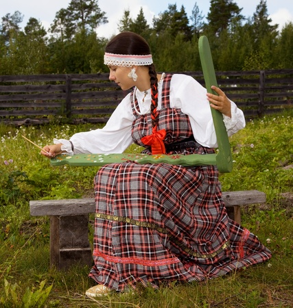 national costume:  Girl in national costume Pomeranian paints distaff  Stock Photo