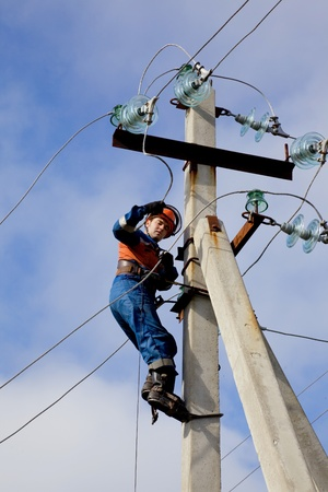lineman: Electrician connects wires on a pole against the blue sky