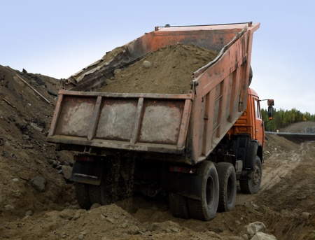 Tipper dumping gravel  for road construction Stock Photo