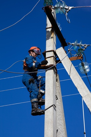 Electrician in overalls rises to concrete pole photo
