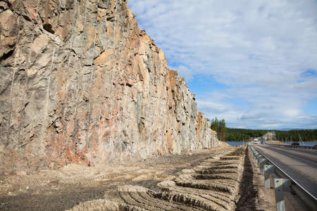 circumstances: The road carved into the rock  Construction of roads in difficult circumstances through the rock in northern Russia Stock Photo