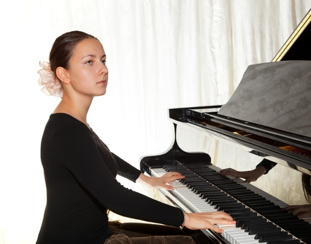 Young beautiful girl playing the piano with a raised lid Stock Photo