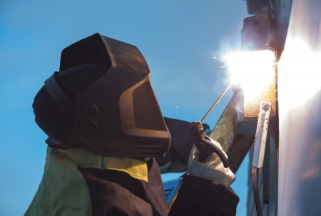 A welder working with metal structure on the background of blue sky