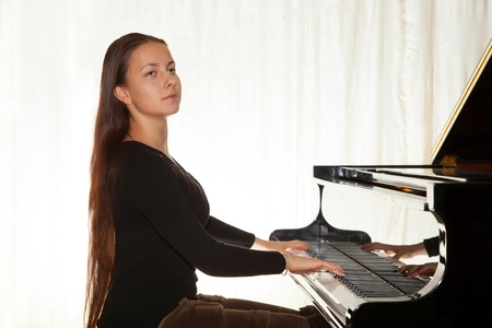 A girl with her hair playing the piano in a concert hall photo