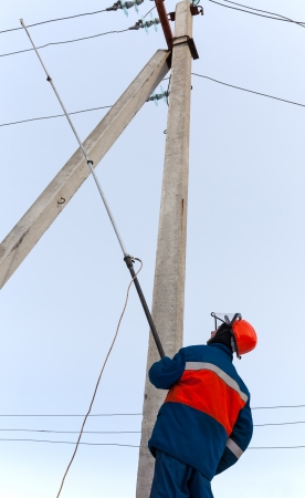 electrician in blue overalls establishes protective earth wire to the power line