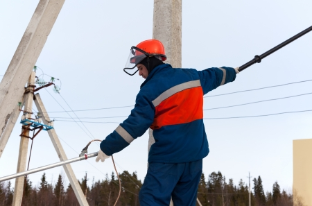 Electrician in blue overalls working on power lines Stock Photo