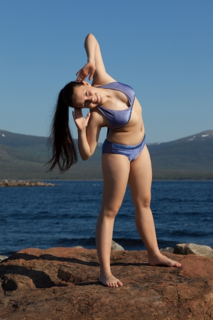 girl in a bathing suit makes charging on the White Sea in the background of mountains and blue sky photo