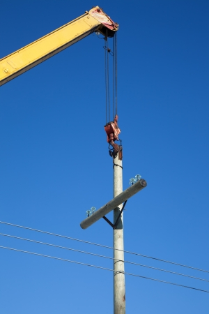 maneuverable: Installation of wooden electric poles crane  When the sunlight against the blue sky