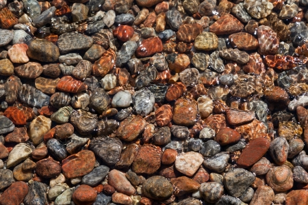 Multi-colored rocks on the shore of the lake lapped by the water in the sunlight photo