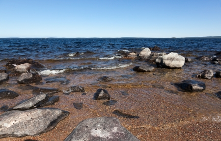 Large gray rocks on the shore of Lake Kolvitsa. Murmansk region. Russia photo
