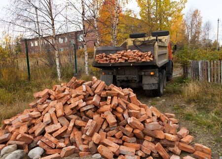 Tipper brought  a lot of red bricks for construction Stock Photo