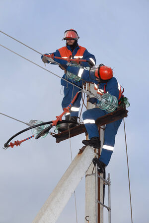Two electrician working on top of an electricity pylon with the use of  ladder and belt Фото со стока
