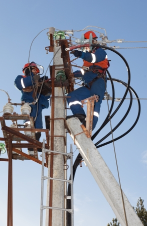 Electricians working on the support of power transmission lines with modern appliances troubleshooting damage