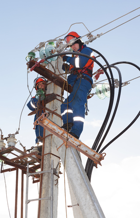 isolator high voltage: Electricians in blue overalls working at height on a support with a lot of wires and insulators