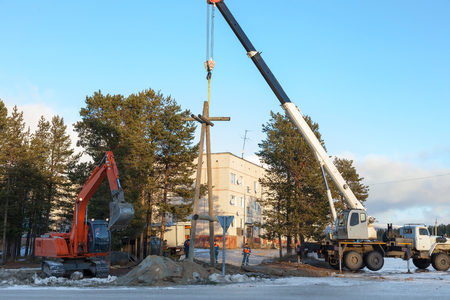 Installing a power pole on the outskirts of the settlements with the use of a truck crane and excavator photo