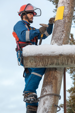 Electrician in blue overalls working on a power line pole in winter photo