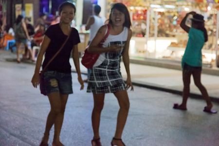 PATONG, THAILAND - APRIL 26, 2012: girls walking in the evening on Bangla Road. Center nightlife  Patong famous Bangla Road. Patong, Thailand, April 26, 2012