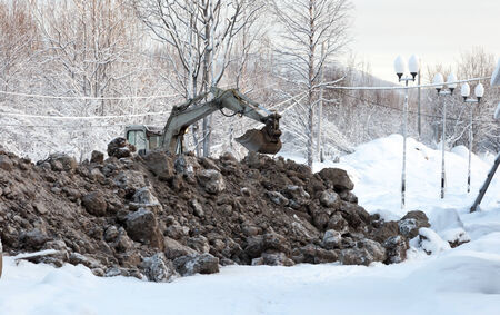 Excavator on a background of a winter landscape digs frozen ground