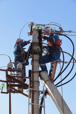 Electricians working at height on a support with linear disconnector and cable XLPE  photo