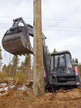 Excavator loader hydraulic tractor digging. Construction of overhead power lines