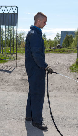 Worker in overalls watering area with water from a hose. covered space