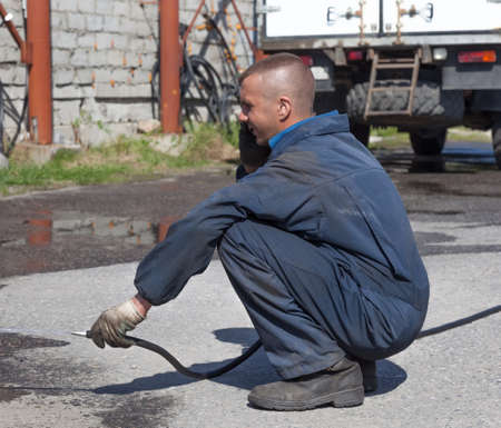 Worker in overalls watering the paved area with water Stock Photo