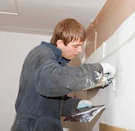 plasterer: Plasterer at indoor renovation decoration with putty knife in stained overalls