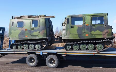 Track SUV on the trailer vehicle for the transportation of tracked vehicles Фото со стока