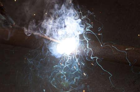 Welding steel pipe, bright light smoke spark electric arc Фото со стока