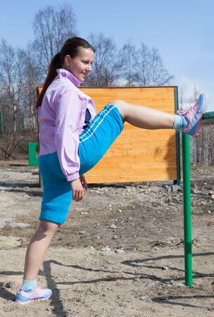 young woman in suit fitness aerobics playing sports on a sunny day