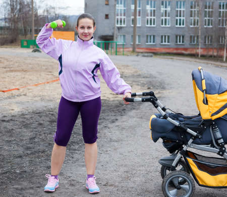 young woman combines sport and a walk with baby in stroller Stock Photo