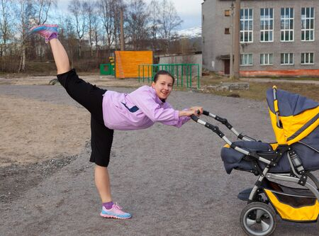 young woman is engaged in aerobics in a stadium combining a walk with baby Фото со стока