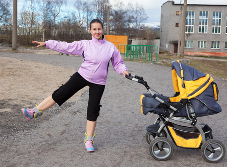 combines: a young mother with a toddler combines walk in a stroller fitness