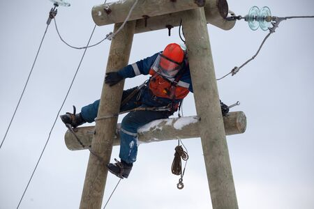 electrician working on top of an electricity pylon with the use of claws-manholes and belt webbing-type