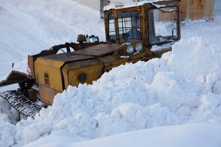 Snow removal in the winter. Tractor with scraper in winter day. The snow-removing machines