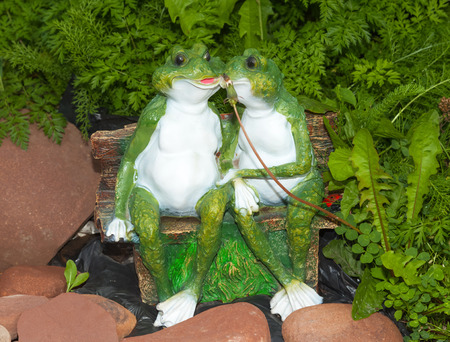Two green ornament frog sitting on a bench near a stones in the tall grass Stock Photo