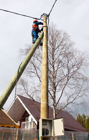 Electrician connects wires on a pole in a country house. Cottage Stock Photo