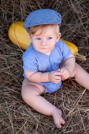 reigns: little boy sits near a haystack in a blue dress and hat, lying next kabachek