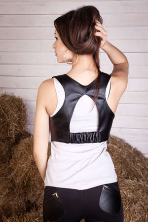 beautiful young girl in a dress in the hay, leather garments, na Stock Photo