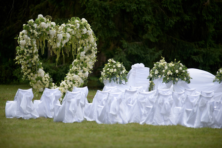 Beautiful white wedding arch decorated with white and green flowers outdoors