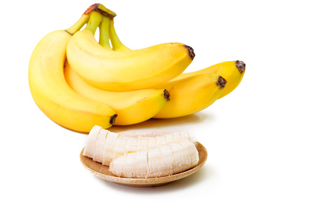 Banana slices on a brown plate and bunch of ripe bananas isolated  and on white background Stock Photo
