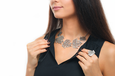 close-up of beautiful woman wearing luxury silver Jewelery. Necklace and finger ring on human model