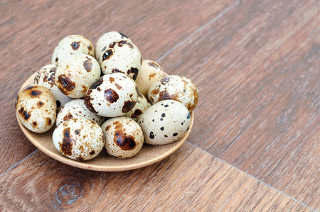 Many Quail eggs in a plate on old wooden table