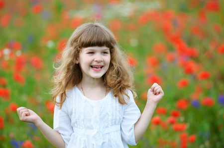 happy and smiling little girl portrait with clenched fists outdoors Stock Photo