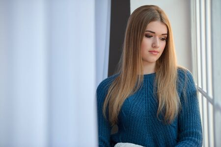 waiting glance: Girl in a blue woolen sweater waiting at the window Stock Photo