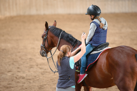 teaches: Girl in helmet Learning Horseback Riding. Instructor teaches teen Equestrian. Stock Photo