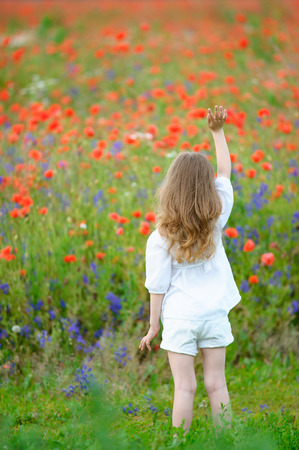 Cute little girl with raised hand to the top. View from the back Stock Photo