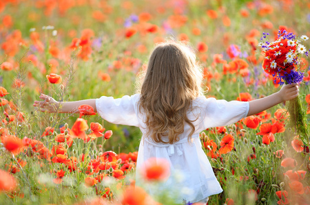 Girl with a bouquet of wildflowers with hands spread to sides. Back view