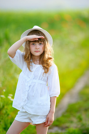 adorable little girl wearing a hat looking into the sky
